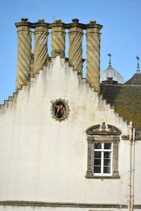 Francis waving from an attic window. Chimneys above. Winton House.