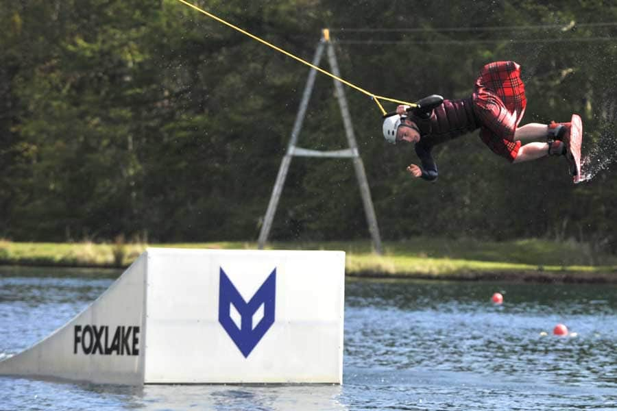 Wake boarding in a kilt at Foxlake Adventures.