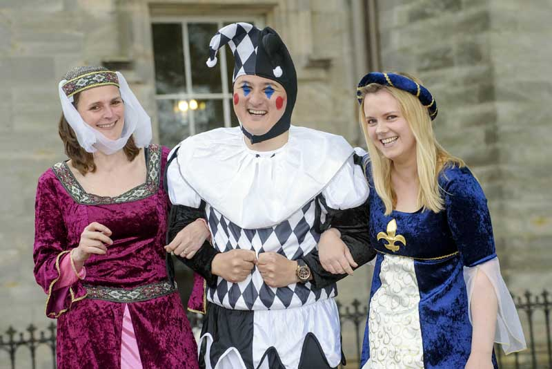 Medieval jester and maids at Winton Castle near Edinburgh