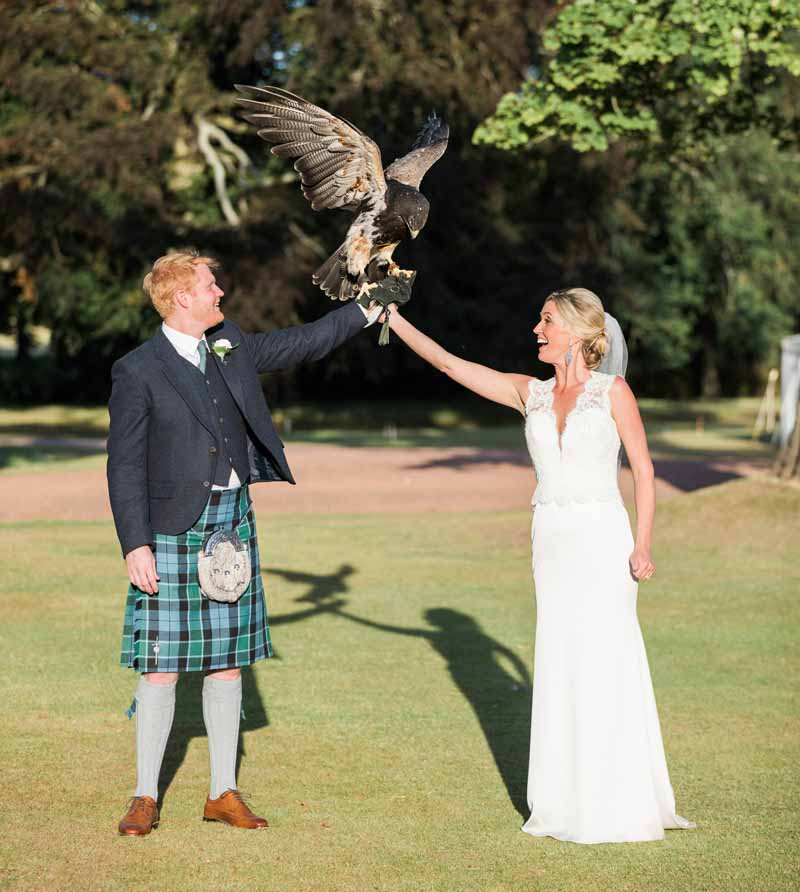 Falconry at Wedding at Winton Castle - bride & groom holding an eagle!
