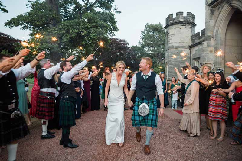 Sparklers and bride and groom outside Winton Castle wedding venue with guests